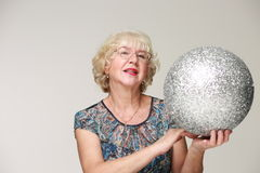 Portrait of an elderly smiling woman with a silver ball Royalty Free Stock Photo