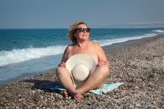 Woman. Portrait of elderly smiling woman that is sitting on beach in straw hat and sunglasses Stock Photography