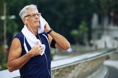Elderly jogger. Portrait of elderly sportsman wiping sweat after jogging royalty free stock photography