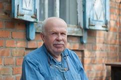Portrait of elderly Ukrainian peasant sitting near his house Royalty Free Stock Photo