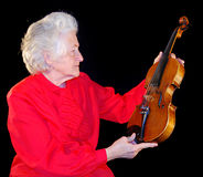 Portrait of elderly woman. Is in red with an age-old violin Royalty Free Stock Images