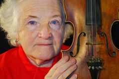 Portrait of elderly woman. Is in red with an age-old violin Royalty Free Stock Photos