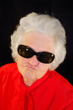A portrait of elderly woman. In red and in antisun glasses Royalty Free Stock Photography