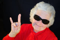 A portrait of elderly woman. In red and in antisun glasses Stock Images