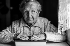 Portrait of an elderly woman with a big book. Black-and-white portrait of an elderly woman with a big book Stock Photography