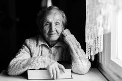 Portrait of an elderly woman with a closed book at the table. Royalty Free Stock Photo