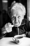 Portrait elderly woman drinking tea. Elderly woman drinking tea. Closeup black and white portrait of russian grandmother Royalty Free Stock Photo
