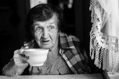 Portrait of an elderly woman drinking tea from a mug Stock Image