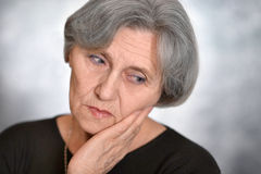 Portrait of an elderly woman. Grieves on a gray background Royalty Free Stock Images