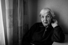 Portrait of an elderly woman in his house. Old lady retired. Black and white photo royalty free stock photography