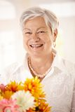 Portrait of elderly woman holding flowers. Closeup portrait of happy elderly woman holding flowers looking at camera, smiling royalty free stock image