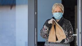 A portrait of an elderly woman in a mask holding food bags. Home delivery in quarantine
