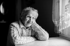 Portrait of an elderly woman near the window. Black-and-white Stock Photo