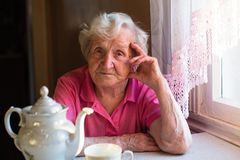 Elderly woman pensioner sitting at a table in the kitchen in his house. Portrait of an elderly woman pensioner sitting at a table in the kitchen in his house stock images