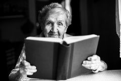 Portrait of an elderly woman reading a book. Royalty Free Stock Photography