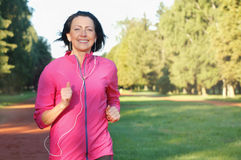 Portrait of elderly woman running with headphones in the park. In early morning. Attractive looking mature woman keeping fit and healthy stock photos