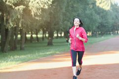 Portrait of elderly woman running in the park stock photo