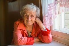 An elderly woman sitting near the window. Royalty Free Stock Photos