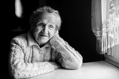 Portrait of an elderly woman sitting near the window. Black-and-white picture stock image