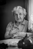Portrait of elderly woman sitting at the table. Royalty Free Stock Photography