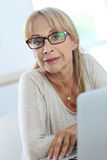 Portrait of elderly woman using laptop Royalty Free Stock Images