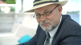 Portrait of eldery man in hat and glasses smiling and nodding on camera. 4K stock video