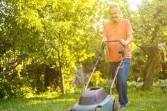 Portrait of eldery senior man working in the summer garden walking on a grass field stock photo