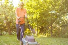 Portrait of eldery senior man working in the summer garden walking on a grass field stock image