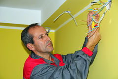 Portrait of an Electrician. Worker installing electrical wiring in a new building - working on the ceiling wires Stock Image