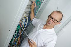 Portrait electrician standing next to fuse board Stock Photos