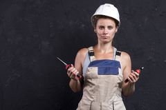 Portrait of electrician woman in uniform and white helmet holds in hand wire-cutters and nippers. Female worker in workwear stock photos
