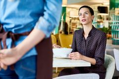 Woman Complaining in Cafe. Portrait of elegant adult women complaining about food quality and taste to young waitress in cafe, copy space royalty free stock photos