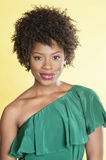 Portrait of an elegant African American in an off shoulder dress smiling over colored background Royalty Free Stock Photo