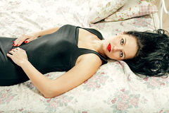 Portrait of elegant beautiful brunette woman lying in bed Royalty Free Stock Photos