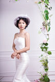 Portrait of elegant bride standing against white wall Royalty Free Stock Images
