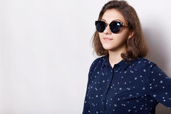 A portrait of elegant brunette wearing sunglasses and stylish shirt having happy expression while posing against white background Royalty Free Stock Photo