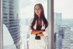 Portrait of elegant business lady wearing white formal suit standing near window looking at camera.  Stock Photo