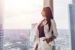 Portrait of elegant business lady wearing white formal suit standing near window looking at cityscape.  Stock Photography