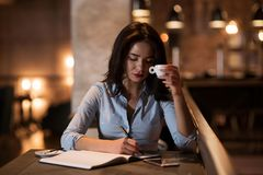 Portrait of an elegant ,concentrated businesswoman drinking coffee and writing the notes in modern restaurant stock photo