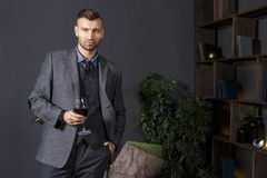 Portrait of elegant confident handsome man in business suit with glass of red wine in luxurious interior. Rich fashionable man with wine in room luxury royalty free stock images