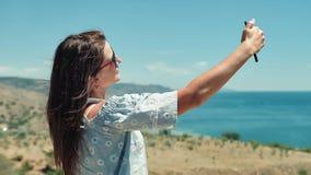 Portrait of elegant European traveler woman taking selfie using smartphone stock video