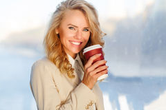 Portrait of elegant happy woman with bright smile holding coffee Royalty Free Stock Photography