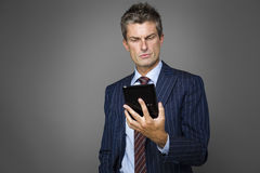 Portrait of elegant pensive businessman watching news. On his tablet Royalty Free Stock Photo