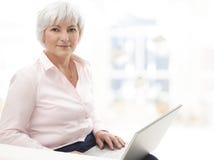 Smiling senior woman working on laptop. Portrait of elegant senior woman working with laptop in living room Stock Image