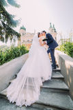 Portrait of elegant stylish young wedding couple kissing on stairs in park. Romantic antique palace at background Royalty Free Stock Photo