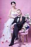 Portrait of elegant wedding couple sitting against pink background Stock Images