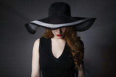 Portrait of elegant woman in black hat and dress. Stock Images