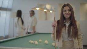 Portrait of elegant woman in formal wear holding billiard cue and looking in camera in front of two blurred male and. Portrait of elegant woman in formal wear stock footage