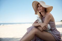 Portrait of an elegant woman relaxing on a beach with her beloved pet royalty free stock photos