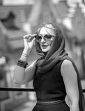 Portrait of elegant woman in scarf and glasses posing on street Stock Photos
